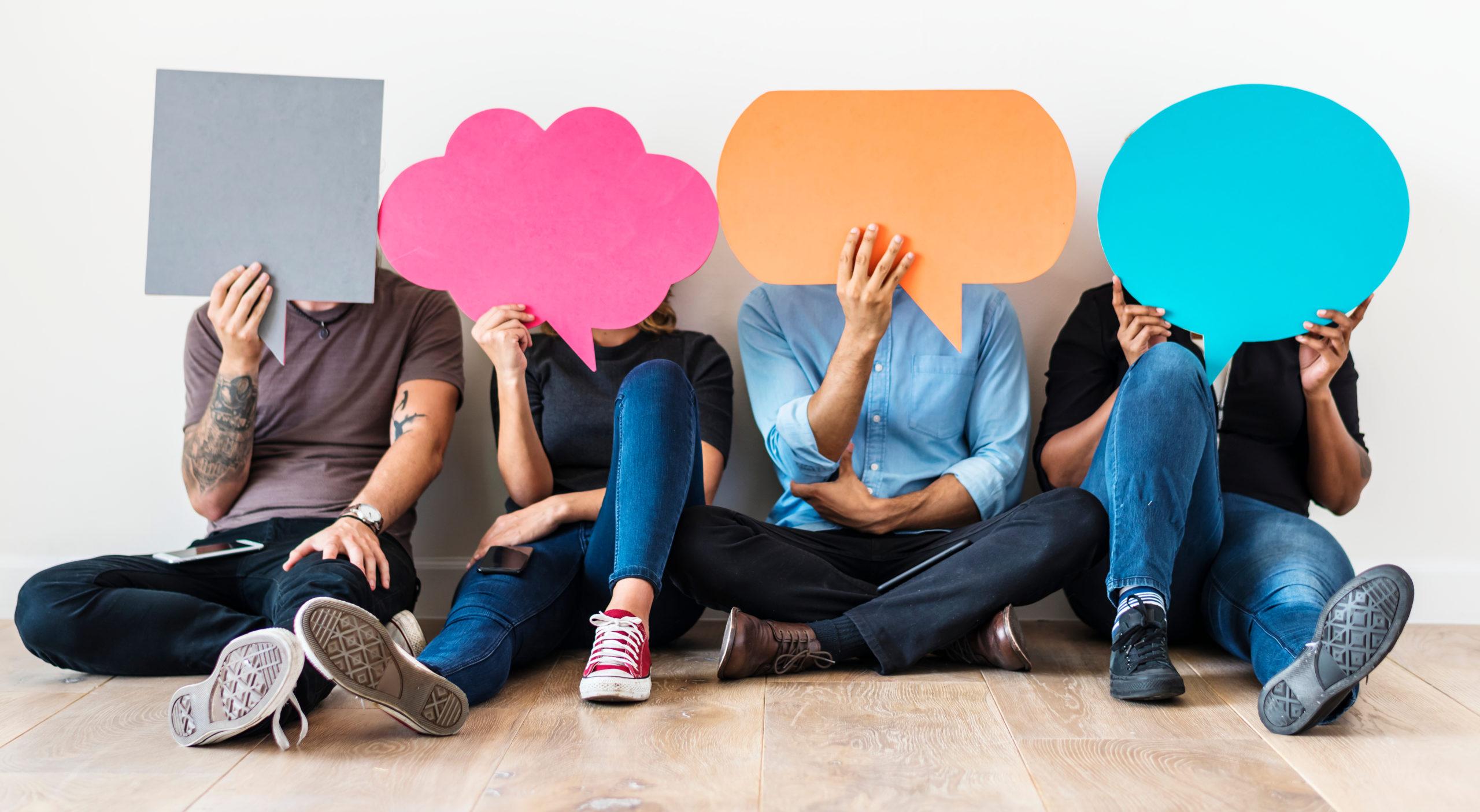 Jeunes tenant des bulles en papier évoquant les pictos d'interaction sur les réseaux sociaux